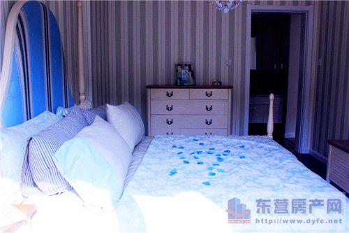 条纹壁纸和浅蓝色的床铺给人